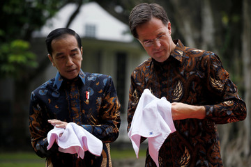 Indonesian President Joko Widodo and Dutch Prime Minister Mark Rutte dry their hands with towels after they plant a tree during their meeting at the presidential palace in Bogor