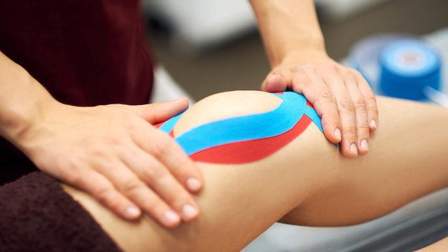 Sports injury kinesio treatment. therapist placing kinesio tape on patient's knee