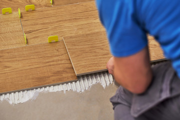 close-up of handyman placing tile spacer. Placing the floor tiles. Home improvement