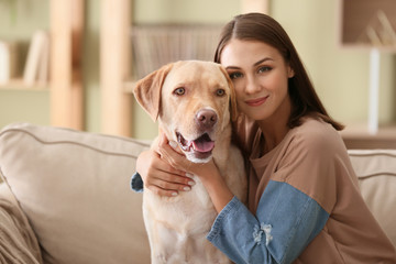Beautiful young woman with cute dog at home