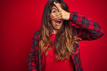 Young beautiful woman wearing casual jacket standing over red isolated background smiling pointing to head with both hands finger, great idea or thought, good memory