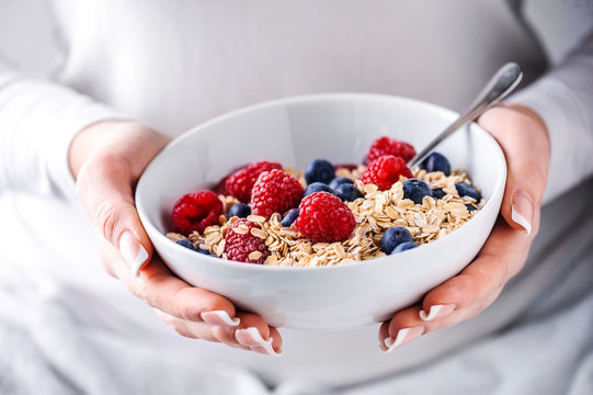 Oat flakes with forest fruits in white plate. Plate full of oat flakes and raspberries, blueberries in woman hands.