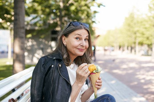 Portrait of fashionable mature European woman eating tasty ice cream cone, sitting outdoors on bench in park, having pleased joyful facial expression, her look expressing delight, saying Yummy