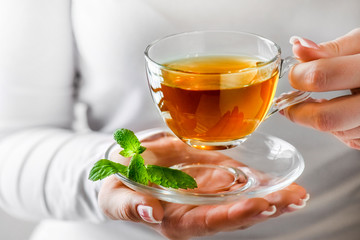 Foto op Canvas Thee Woman holding cup of green tea in glass cup. Hot tea with mint leaf in glass jar or cup.