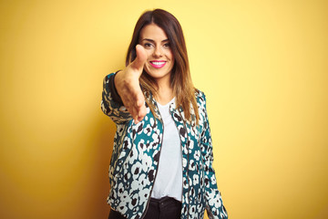 Young beautiful woman wearing casual jacket over yellow isolated background smiling friendly...