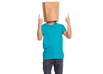 Fototapete - Portrait of teen boy with paper bag over head pointing hands up at copyspace, isolated on white background. Child pointing fingers at something.