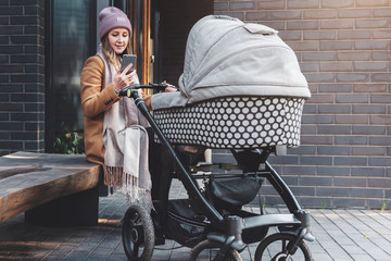 Woman with baby stroller walking,sitting on bench, using smartphone for online communication.Girl texting messages, watching video