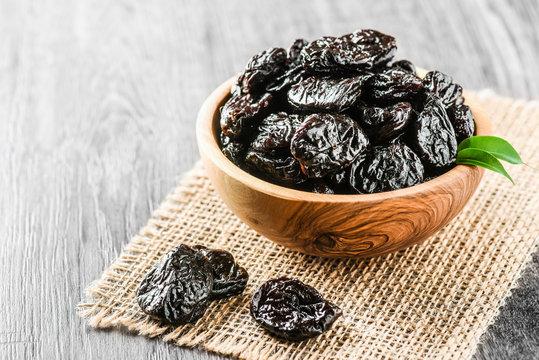 Fresh prunes in wooden bowl. Prunes on stone dark table. Prunes healthy food. Dried plums.