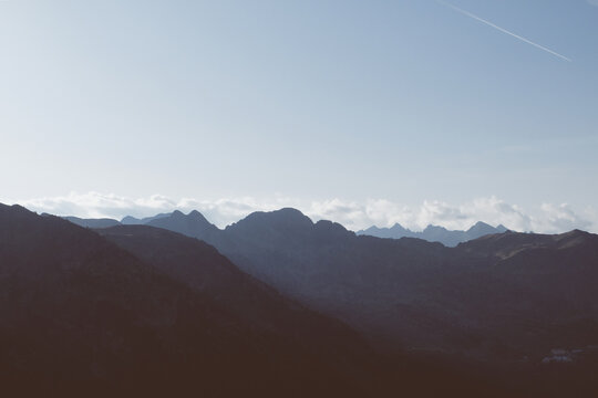 Beautiful alpine landscape with mountain range silhouette during sunset.
