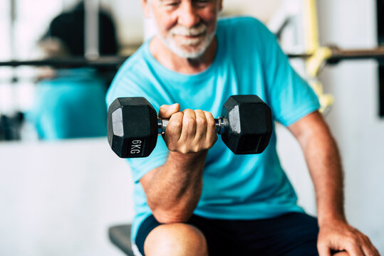 adult man and mature senior at the gym working his body with dumbbell - one man hapy training indoors sitted on the bench
