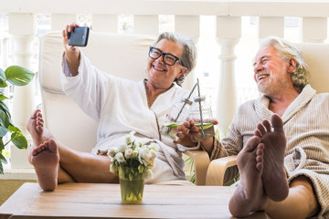 couple of seniors or mature people in a resort spa in their hotel or house clinking with their cocktail and taking a salfie with her phone - having fun with feet on the table looking between they