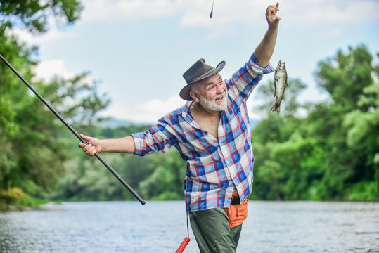 Hobby sport activity. Fish farming pisciculture raising fish commercially. Pensioner leisure. Fish on hook. Man senior fisherman. Fisherman fishing equipment. Fisherman alone stand in river water