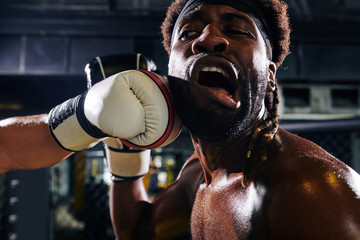 Close-up image of boxer getting punch to the jaw during match in boxing cage