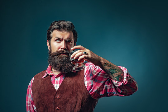 Whiskey. Fashionable man in white shirt and suspenders. Luxury beverage concept.
