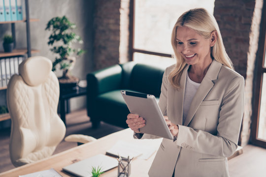 Profile side photo of charming middle aged freelancer marketer lawyer use her tablet read information from her employees investors clients wear blazer in workstation office