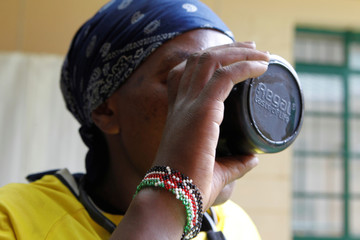 Drug addict drinks water after taking methadone at a Medication Assisted Therapy clinic at Karuri hospital in Kiambu