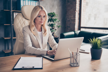 Photo of blonde haired old successful woman readying to hold online conference at mastering enlglish for her students using wireless internet connection