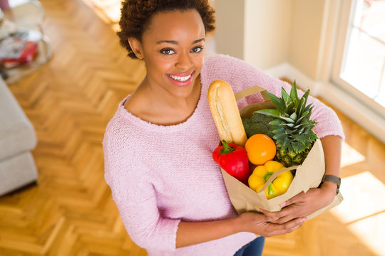 Young beautiful african american woman holding paper bag full of fresh healthy groceries