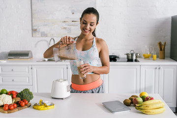 happy sportswoman pouring smoothie into glass near fruits and vegetables