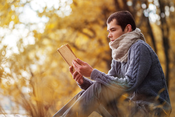 A young man in a warm knitted sweater and scarf Snood reading an old book in the autumn Park . Lifestyle