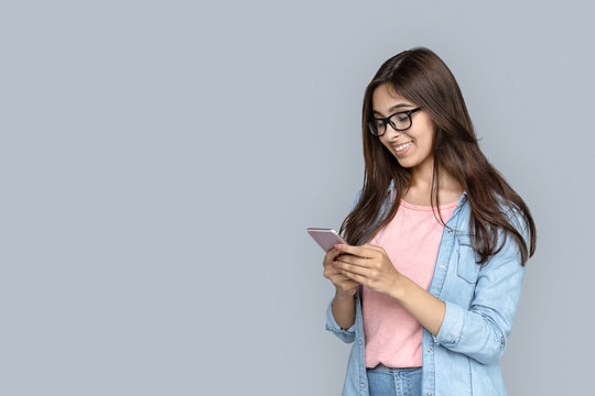 Happy smiling young adult indian woman hold modern smart phone in hands, looking at display screen texting messages using online social media apps standing isolated on grey background with copy space