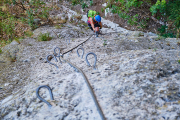 Strong, fit woman climbing a vertical section on via ferrata at Turda gorge (Cheile Turzii) Romania - view from above.