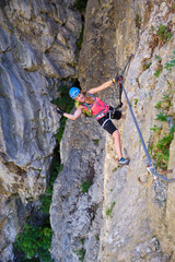 Smiling woman hanging from a via ferrata steel cable at Turda gorge (Cheile Turzii), Romania, during the ascent through Hili cave.