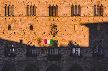 Gothic Front facade of medieval stony town hall in Pistoia Tuscany Italy at sunset with medici family crest and italian flag