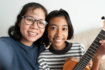 Close-up of an Asian mother and daughter taking a selfie and smiling while sitting on the sofa. The little girl holding a ukulele with her left hand in the living room at her home.