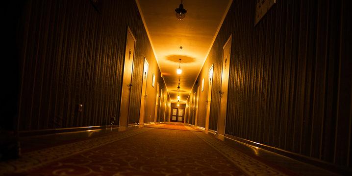 long dark vintage motel corridor with closed doors