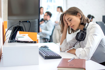 Young attractive woman operator with headset over neck suffering from headache