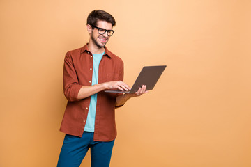 Portrait of his he nice attractive cheerful cheery successful smart clever intelligent brunet guy consultant agent broker holding in hands laptop isolated over beige color pastel background