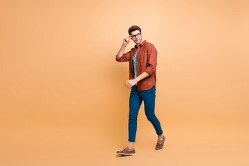 Full length body size profile side view of his he nice attractive trendy calm brunette guy business assistant shark expert touching specs walking isolated over beige color pastel background