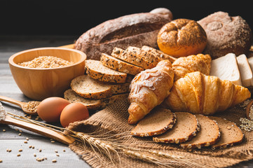 Different kinds of bread with nutrition whole grains on wooden background. Food and bakery in kitchen concept. Delicious breakfast gouemet and meal.