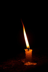 Burning Single Candle At Night. One candle background stock photo burning high flame isolated in black background. Concept for diwali, christmas, church, ritual, temple, loneliness, believer, protest.