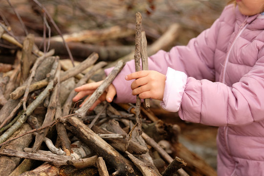 Mid section of a 4 year old child girl in purple warm clothing building something with wooden sticks in the autumn forest on a moody day in October in Germany