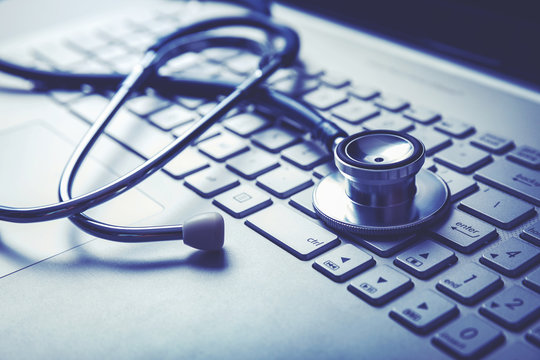 medical stethoscope on laptop keyboard. computer diagnostics or e-health concept