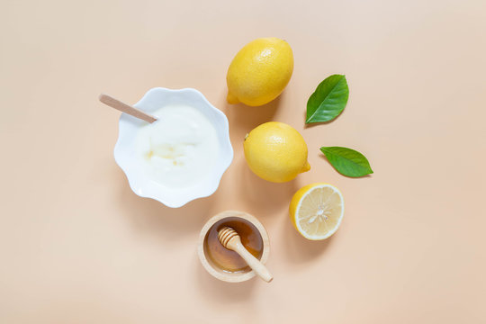 Perfect homemade natural face mask ingredients for bright and healthy skin. Top view of yogurt, lemon and honey on orange background. Beauty herbal skincare product concept. Flat lay.