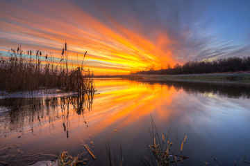 Beautiful sunrise over the pond at winter, Poland