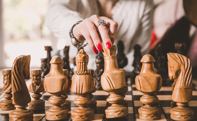 woman hand taking white king figure from opposite side chessboard