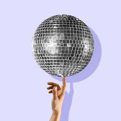 An alternative music. Touch the beauty. Hand holding disco ball on purple background. Negative space to insert your text. Modern design. Contemporary colorful and conceptual bright art collage.