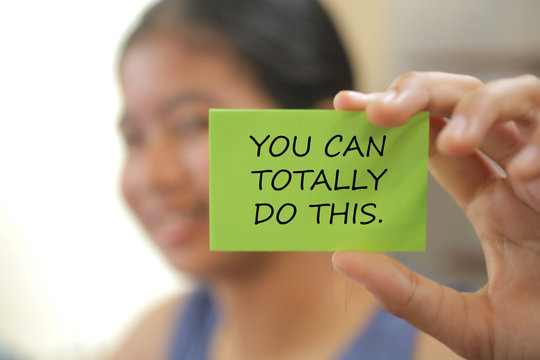 Blurry image of young girl holding a motivation sign with text on it - you can totally do this.  encouragement and self improvement concept.