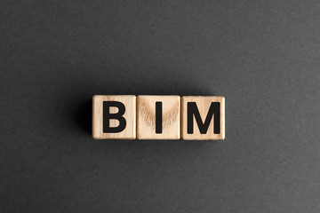 BIM - acronym from wooden blocks with letters, abbreviation BIM Building Information Modeling concept, gray background