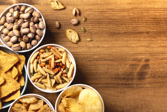 Pile of varied beer snacks in bowls on a wooden table, top view, flat lay. Nachos, pistachios, chips and other beer snacks on a wooden background, copy space.