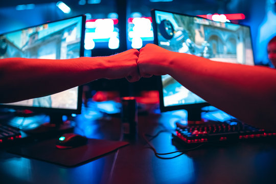 Professional gamer greeting and support team fists hands online game in neon color blur background. Soft focus, back view
