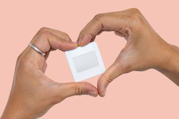Hands in heart form love slide film mount frame on pink background.