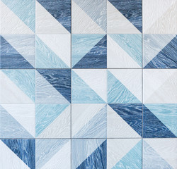 Modern ceramic tile with geometric pattern and imitation of wood texture in gray and light blue colors.