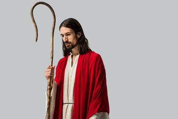 sad man in jesus robe holding wooden cane isolated on grey