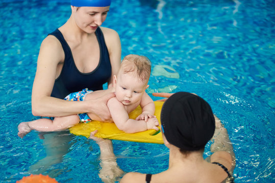 Baby in swimming nappies lying down on floating board on surface of turquoise water. Swimmer master carrying out swimming courses for moms and babies in pool. Young women watching for little child