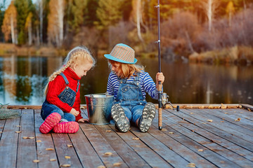 Two little sisters or friends sit with fishing rods on a wooden pier. They caught a fish and put it in a bucket. They are happy with their catch and discuss it.